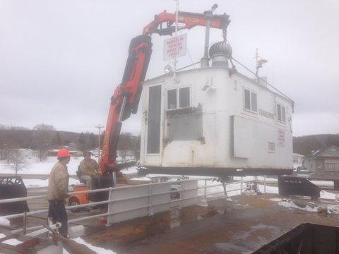 Workers remove the old wheelhouse from the Ironton Ferry earlier this spring. Extensive work on the vessel is now finished and a final inspection is scheduled for today, Monday.