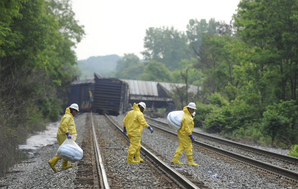 Workers are shown near the scene of yesterday's train derailment.