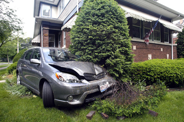 A car, driven by the resident of this house in the 7000 block of Ashland Avenue in River Forest, rests embedded in shrubbery. The driver lost control of the car after pulling out of the unattached garage. Fire officials said the man was transported to Loyola Medical Center in Maywood.