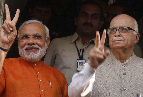 Gujarat Chief Minister Narendra Modi, left, flashes a victory sign as he sees off Bharatiya Janata Party (BJP) senior leader Lal Krishna Advani, right, after a meeting in December 2012 in Ahmadabad, India. Advani, one of the founding members of India's main opposition party, resigned from all party positions Monday, a day after the party appointed Modi to lead its campaign in national elections next year.