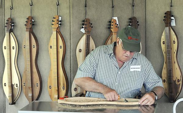 Jim Good of Walton, WV carves a dulcimer body out of chestnut wood at the 2006 Mountain Heritage Arts & Crafts Festival. This year's festival opens Friday, June 14.