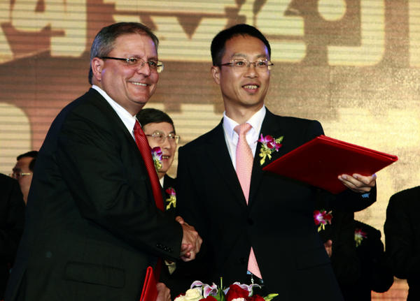 Gerry Lopez, chief executive of AMC Entertainment Holdings, left, shakes hands with Zhang Lin, vice president of Dalian Wanda Group, during a Beijing signing ceremony for Dalian Wanda to acquire AMC Entertainment.