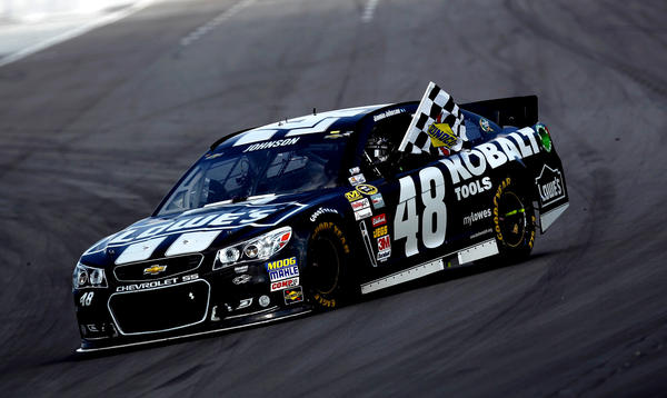 Jimmie Johnson celebrates with the checkered flag after winning the Party in the Poconos 400 at Pocono Raceway.