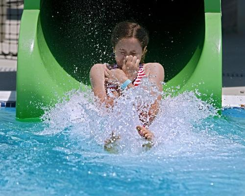 Destiny Whitlock, 13 of Burbank, comes out of one of two water slides during the grand opening of the Verdugo Pool in Burbank on Saturday.