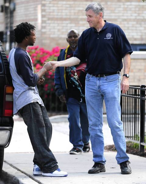 Brother Jim Fogarty, one-half of the community outreach group Brothers and Sisters of Love, chats with a youth on Chicago's North Side near the remaining row houses of the former Cabrini-Green housing project.