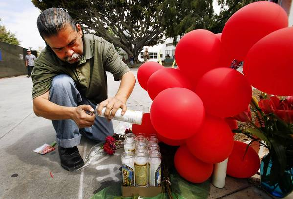 Rafael Torres, son of Santa Monica College shooting rampage victim Margarita Gomez, lights candles Monday morning at a memorial created where his mother was killed. The campus was open as Santa Monica College students returned to classes Monday for the first time since the deadly rampage.