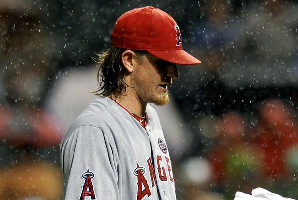 Angels pitcher Jered Weaver requests a towel as rain falls in the fourth inning of Monday's game against the Baltimore Orioles.
