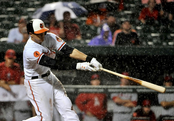 Baltimore Orioles' Manny Machado hits a single in the sixth inning, scoring Nate McLouth, against the Angels.