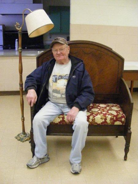 Jerry German sits on a bench that he made out of pieces of an old bed for the upcoming furniture sale in Guelph, N.D. This piece and many more will be sold during a turkey barbecue July 7 to benefit the Guelph Community Center.