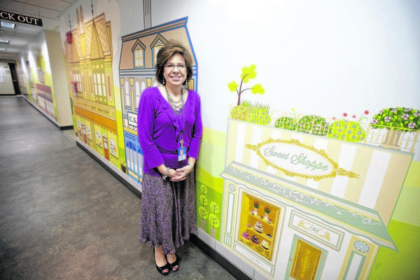 Elaine Karaszewski, health centers manager at Memorial Medical Group, poses inside Centennial Neighborhood Health Center, 621 Memorial Drive, South Bend. The clinic incorporates a mural depicting small-town storefronts and shops to create a community feeling.