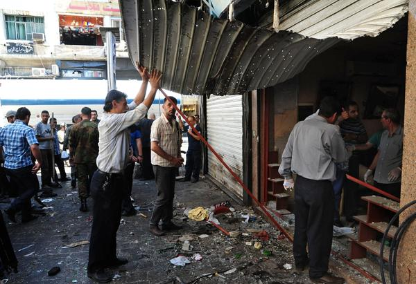 Men inspect a damaged shop at the scene of two explosions in Damascus, Syria.
