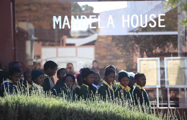 Schoolchildren line up Monday to visit the house of Nelson Mandela in the Soweto district of Johannesburg, South Africa. The 94-year-old Mandela remained in a Pretoria hospital for a sixth day after a recurrence of a longstanding lung infection.
