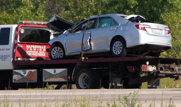 Crews work to remove a silver Toyota from the scene of a crash involving a semi along the westbound lanes of Interstate 88 near Eola Road on Tuesday. The crash briefly closed both directions of the tollway to allow a medical helicopter to land to transport a victim to an area hospital.