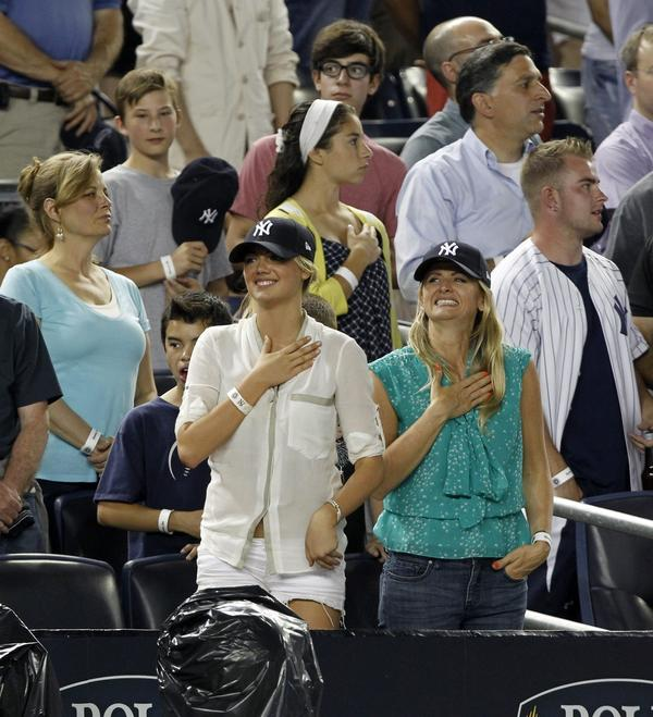 Kate Upton smiles while standing for the National Anthem before the New York Yankees versus the Boston Red Sox game at Yankees Stadium in the Bronx.