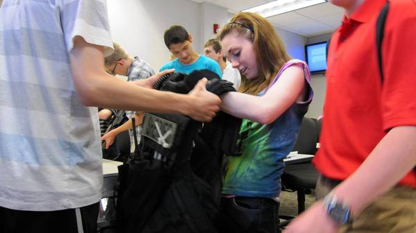 Teens take turns trying on a SWAT team vest during the first St. Charles Police Department Youth Police Academy.