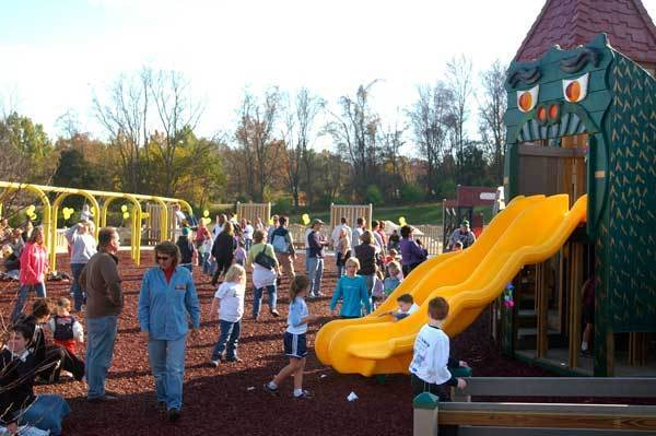 Children and parents enjoy some playtime after the ceremony officially opening Annie's Playground in Fallston