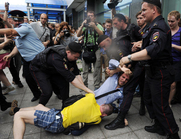 Russian police officers separate a protester and a gay rights activist clashing outside the lower house of parliament in Moscow.