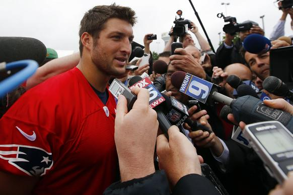 Newly-signed New England Patriots quarterback Tebow talks to reporters following practice session during mandatory team mini-camp in Foxborough