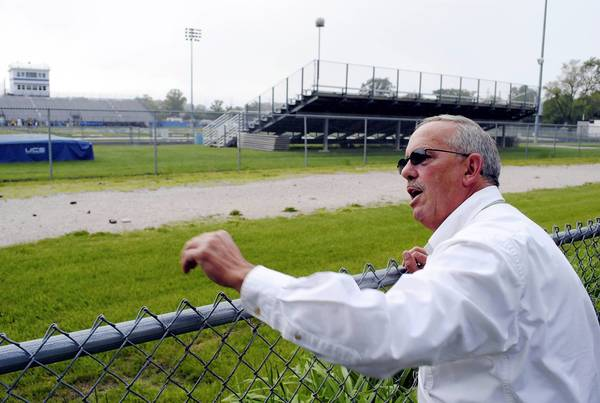 Kevin Fassett leans against the fence in his yard, which looks out onto the 20 yard line of Wolters Field, where Highland Park High School plays its home football games, among other sporting events.
