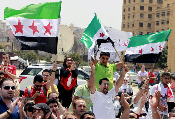 Lebanese and Syrian activists hold Syrian revolution flags during a protest in Beirut against the participation of Hezbollah in the Syrian war.