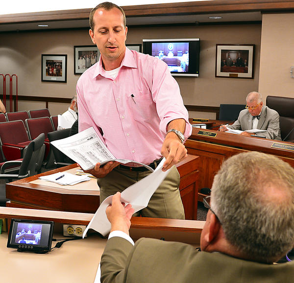 Jason Divelbiss distributes handouts Tuesday to the Washington County Board of Commissioners for a discussion of the adequate public facilities ordinance. Divelbiss is part of a development team of a parcel in West Hagerstown between Salem Avenue and Maugansville Road.