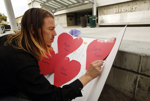Nate Edelson, 39, makes his own memorial sign Monday in front of the closed Santa Monica College Library to honor the victims of last week's deadly shooting rampage.