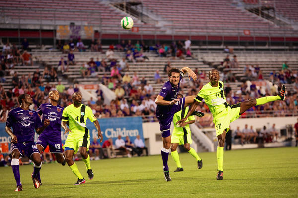 Players chasing the ball during the soccer Game between the Orlando City Lions and the Antigua Barracudas. held at the Citrus Bowl on June 9, 2013.