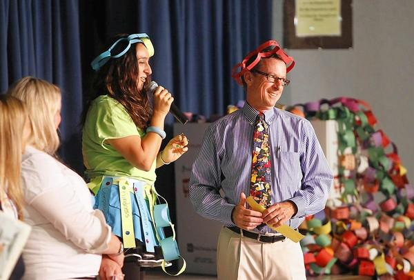 Third-grade teacher Azadeh Baghai, left, says a few words about Principal Ron LaMotte, right, as he is given the staff recognition award during the Rachel's Challenge assembly at Top-of-the-World on Tuesday.