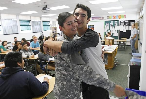 U.S. Army Pvt. 2 Tyler Davis, 19, a former cheerleader at Costa Mesa High School, surprises her brother Trevor Davis, 16, during a literature class on Tuesday.