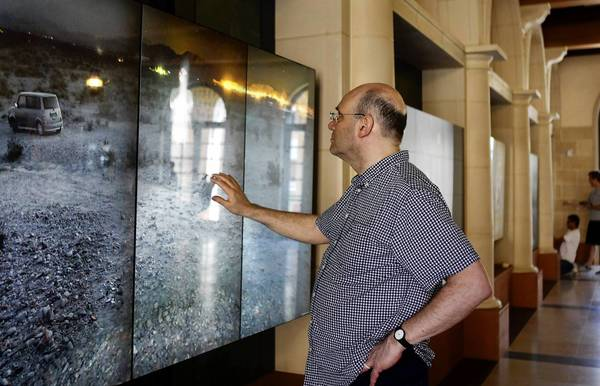 Perry Hoberman, associate research professor at the USC School of Cinematic Arts, interacts with a touch screen in the lobby of the new building.