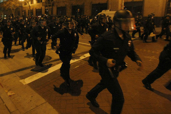 In this image from November 2011, LAPD officers rush down Spring Street in a show of force during the Occupy L.A. protests.