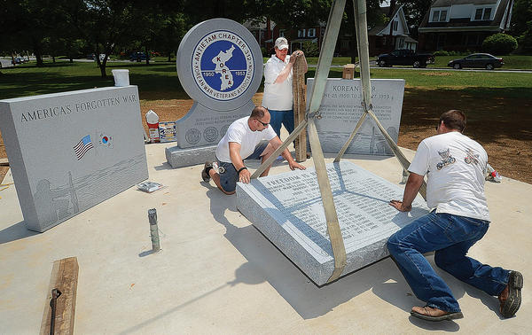 Paul Peer, left, Rick Freeman and Dave Burkett guide a tablet stone to its resting place at the site of the new Korean War Memorial at Mealey Parkway and Potomac Avenue in Hagerstown. The crew works for Greencastle Bronze and Granite Inc.