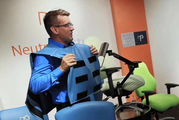 Neutral Posture customer service director Brock Neville shows how to use the Guardian chair and bulletproof vest Monday at the NeoCon office furniture expo in Chicago.