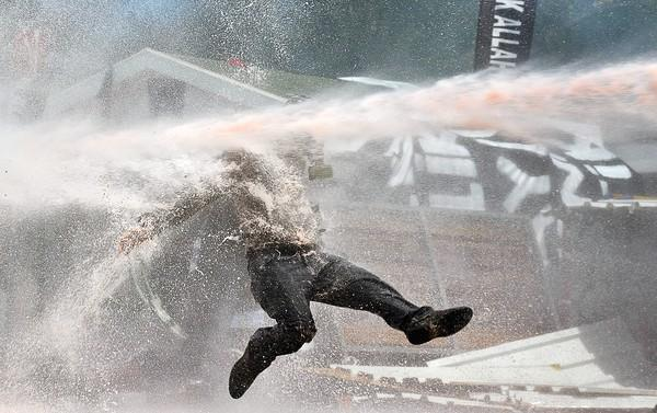 A protester is hit by water from a cannon during clashes in Taksim Square in Istanbul, Turkey.