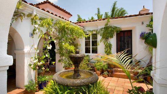 The gated hacienda recently sold by actress Debi Mazar opens to a central courtyard with pavers and a fountain.