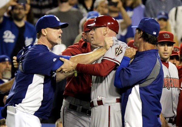 Dodgers hitting coach Mark McGwire, left, and Dodgers Manager Don Mattingly grab onto Arizona Diamondbacks third base coach Matt Williams after Dodgers starting pitcher Zack Greinke was hit by a pitch and both benches cleared.