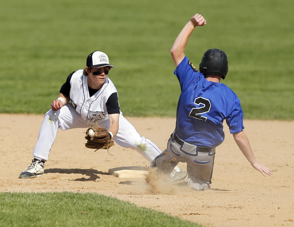 Jacob Carrels of the Aberdeen Smittys, left, readies to put a tag on Matt Koch of Sioux Falls Post 307 as Koch tried to steal second base during Tuesday's first game at Fossum Field. Koch was out on the play.