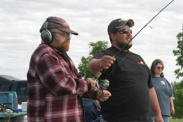 Steve Painter (plaid) reels in the first fish of the evening with a little help from Blake Ketterling, president of the Northeastern South Dakota Walleye Club,