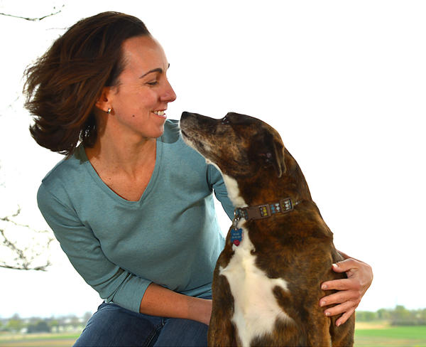 Maria Mestre, owner of Southpaws in Hagerstown's North End, snuggles with canine friend Maggie. The pet-sitting and dog-walking service opened July 3, 2012.