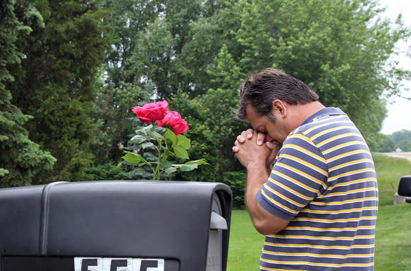 Area resident Kelly Glisan prays after placing flowers on the mailbox in front of a house on the 500 block of Oldfield Road in Darien today. Four people were found fatally shot Tuesday inside the house.