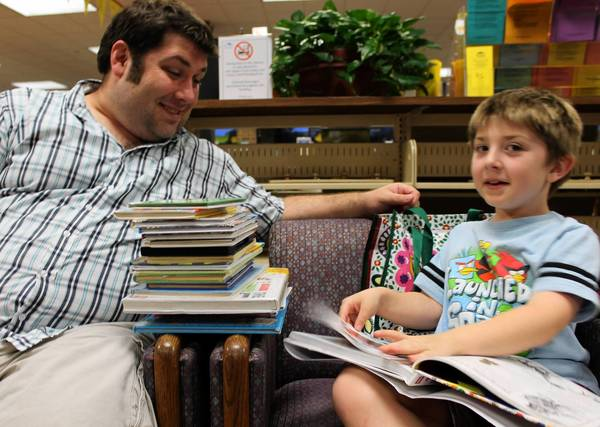 Zach Wittenborn, 7, of Naperville, reads a book with his father, David, during extended Sunday evening hours at Nichols Library.