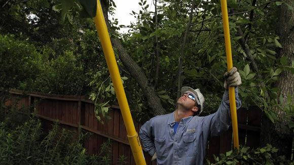 Com Ed lineman Derek Livingston checks downed wires at Kensington and Westgate Roads in Mt. Prospect after June 2011 storms.