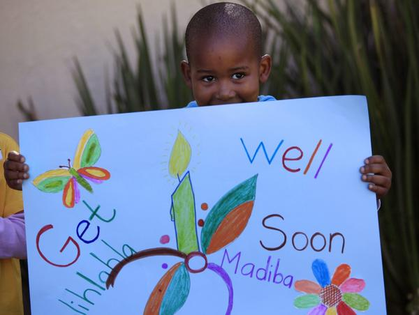 A boy holds up a get-well poster for South Africa's former president, Nelson Mandela, at his house in Johannesburg.