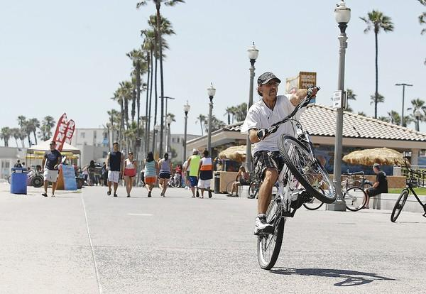 A bicyclist rides at the beach trail north of the Huntington Beach Pier on Monday.