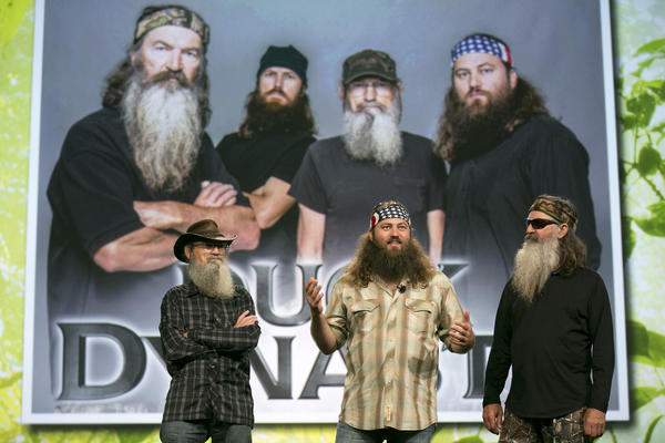 "Robertson family members stand in front of Robertson family members in a promotional appearance for ""Duck Dynasty."""