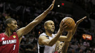 Spurs' Parker drives to the net between Heat's Bosh and Chalmers during Game 3 of their NBA Finals basketball playoff in San Antonio