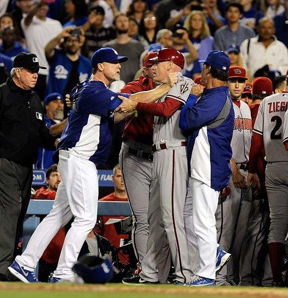 Dodgers hitting coach Mark McGwire, left, grabs Arizona coach Matt Williams after the Diamondbacks' Ian Kennedy hit Zack Greinke with a pitch.
