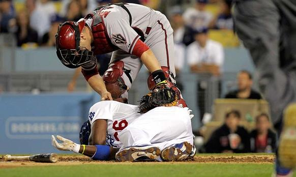Arizona Diamondbacks catcher Miguel Montero (26) tends to Los Angeles Dodgers right fielder Yasiel Puig (66), who was hit by a pitch thrown by Arizona Diamondbacks starting pitcher Ian Kennedy (31) in the sixth inning.