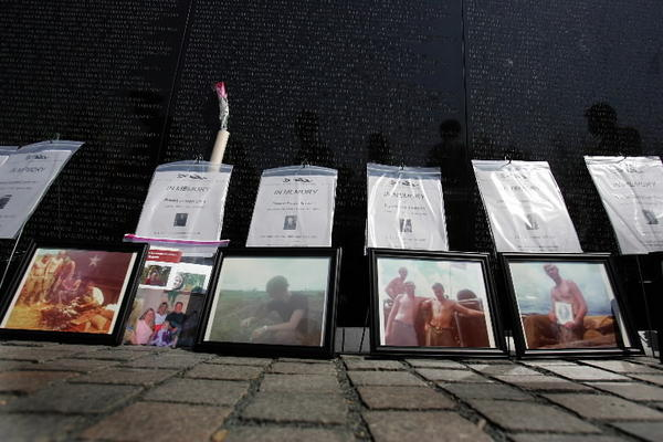 Photographs placed at The Wall in Washington, D.C. in tribute to service members who died after serving in the Vietnam War. Family members read aloud the names of their loved ones during the National In Memory Day Ceremony. The service members who were included did not meet U.S. Department of Defense guidelines for inclusion on The Wall, but organizers said the honorees died of war-related ailments.