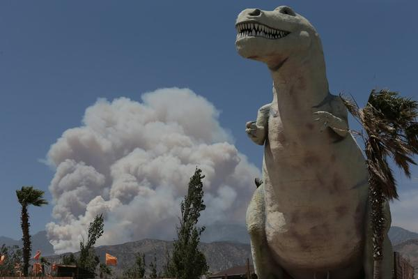 A fire burns in Hathaway Canyon, a few miles from the World's Biggest Dinosaurs theme park in Cabazon.